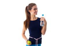 Femme de centimètre autour de sa taille tenant la pomme et l'eau Photographie stock