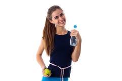 Femme de centimètre autour de sa taille tenant la pomme et l'eau Image libre de droits