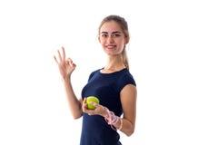 Femme de centimètre tenant une pomme et montrant correct Image libre de droits