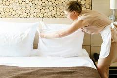 Femme de chambre faisant un lit dans une chambre d'hôtel Photographie stock
