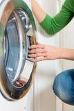 Femme de charge avec la machine à laver Photo stock