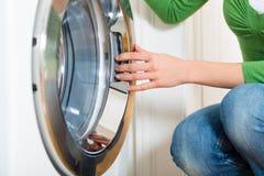 Femme de charge avec la machine à laver Photographie stock