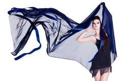 Femme de charme avec la mousseline de soie de soufflement Images stock