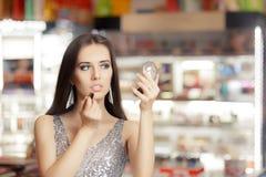 Femme de charme avec le miroir de rouge à lèvres et de maquillage photo libre de droits