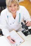 Femme de chercheur senior travaillant avec le microscope Image stock