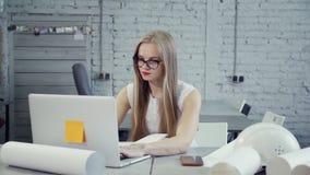 Femme de cheveux blonds travaillant sur l'ordinateur portable moderne dans le bureau clips vidéos