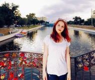 Femme de cheveux de gingembre se tenant sur le pont de l'amour avec beaucoup de serrures accrochant sur la barrière Photo libre de droits