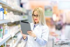 Femme de chimiste de pharmacien se tenant dans la pharmacie de pharmacie, souriant et à l'aide du comprimé photographie stock