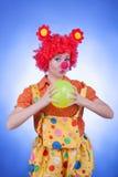 Femme de clown avec une boule sur le fond bleu Image libre de droits