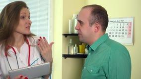 Femme de conseiller médical donnant des résultats d'essai patients d'homme sur le comprimé numérique banque de vidéos