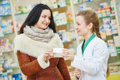 Femme de consultation de chimiste de pharmacie dans la pharmacie Image stock