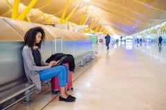 Femme de couleur à l'aéroport utilisant le comprimé et musique de écoute avec Photos stock