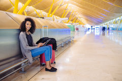 Femme de couleur à l'aéroport utilisant le comprimé et musique de écoute avec Photographie stock