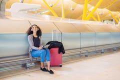 Femme de couleur à l'aéroport utilisant le comprimé et musique de écoute avec Images stock