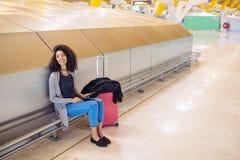 Femme de couleur à l'aéroport utilisant le comprimé et musique de écoute avec Photo stock