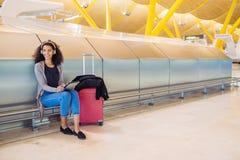 Femme de couleur à l'aéroport utilisant le comprimé et musique de écoute avec Photos libres de droits
