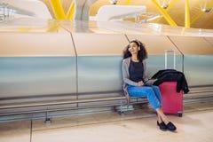Femme de couleur à l'aéroport utilisant le comprimé et musique de écoute avec Images libres de droits