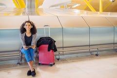 Femme de couleur à l'aéroport utilisant le comprimé et musique de écoute avec Image libre de droits
