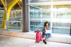 Femme de couleur à l'aide du téléphone portable et de l'ordinateur portable à la séance d'aéroport Photographie stock