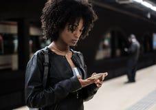 Femme de couleur à l'intérieur de la station de métro attendant le train Photographie stock libre de droits
