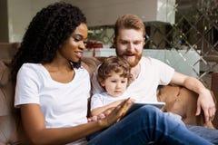 Femme de couleur africaine heureuse avec la famille blanche détendant et regardant l'écran de comprimé photo stock