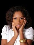 Femme de couleur assez jeune avec des mains le long de visage image stock