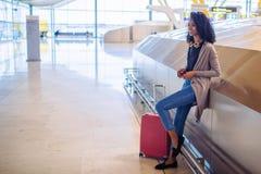 Femme de couleur attendant son vol utilisant le téléphone portable à l'aéroport Photographie stock