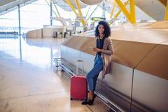 Femme de couleur attendant son vol utilisant le téléphone portable à l'aéroport Photos libres de droits