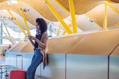 Femme de couleur attendant son vol utilisant le téléphone portable à l'aéroport Image libre de droits