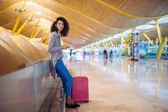 Femme de couleur attendant son vol utilisant le téléphone portable à l'aéroport Images libres de droits