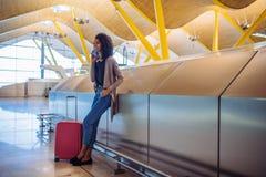 Femme de couleur attendant son vol utilisant le téléphone portable à l'aéroport Image stock