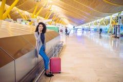 Femme de couleur attendant son vol utilisant le téléphone portable à l'aéroport Images stock