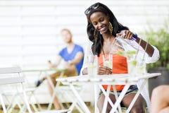 Femme de couleur attirante s'asseyant à une table de café dehors et au drin Images libres de droits
