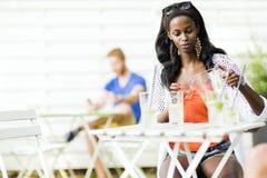 Femme de couleur attirante s'asseyant à une table de café dehors et au drin Photo libre de droits