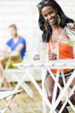 Femme de couleur attirante s'asseyant à une table de café dehors et au drin Image stock