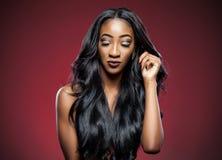 Femme de couleur avec de longs cheveux brillants luxueux Images stock