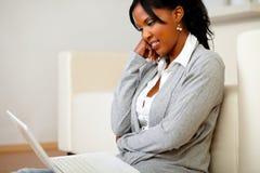 Femme de couleur avec du charme s'asseyant sur l'étage Images libres de droits