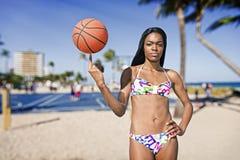 Femme de couleur avec le basket-ball sur son doigt, à un champ de basket-ball Image stock