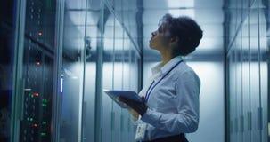 Femme de couleur avec le comprimé fonctionnant dans la chambre de serveur images libres de droits