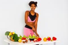 Femme de couleur coupant Paprica posant derrière une table complètement des vegatebles et des fruits d'isolement sur le fond d'im image libre de droits