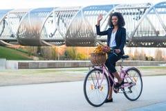 Femme de couleur d'affaires montant une bicyclette de vintage dans la ville photo libre de droits