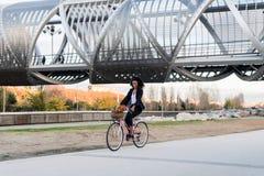 Femme de couleur d'affaires montant une bicyclette de vintage dans la ville photos stock