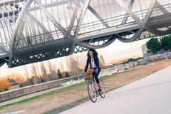 Femme de couleur d'affaires montant une bicyclette de vintage dans la ville images libres de droits
