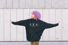 Femme de couleur de métis avec des cheveux Afro pourpres et un swea de New York Image libre de droits