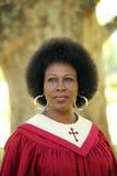 Femme de couleur en d'église de robes longues verticale rouge à l'extérieur Photographie stock