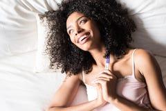 Femme de couleur heureuse avec un essai de grossesse sur le lit Photo stock