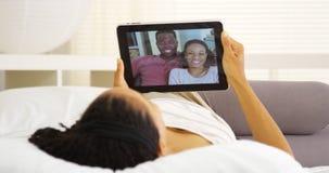 Femme de couleur heureuse causant avec des amis sur le comprimé Image libre de droits