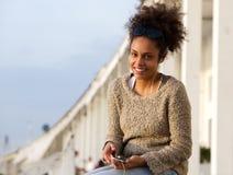 Femme de couleur heureuse s'asseyant dehors avec le téléphone portable photo libre de droits