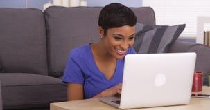 Femme de couleur heureuse surfant l'Internet Images stock