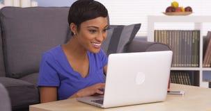Femme de couleur heureuse surfant l'Internet Photographie stock libre de droits